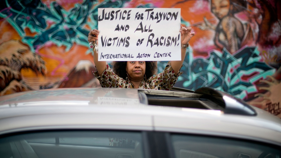 Hope Jones, of Atlanta, steps out of her car with a sign while stopped at a traffic light to join demonstrators marching by protesting the day after George Zimmerman was found not guilty in the 2012 shooting death of teenager Trayvon Martin, Sunday, July 14, 2013, in Atlanta. (AP / David Goldman)