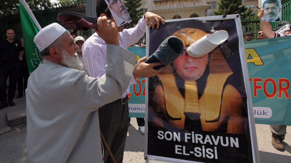 """Turkish supporters of ousted Egyptian President Mohammed Morsi hit a portrait of Egyptian military chief Gen. Abdel Fattah al-Sisi, depicted as the """" last pharaoh """", with their slippers, as they stage a protest outside the Egyptian embassy in Ankara, Turkey, Saturday, July 13, 2013. (AP / Burhan Ozbilici)"""