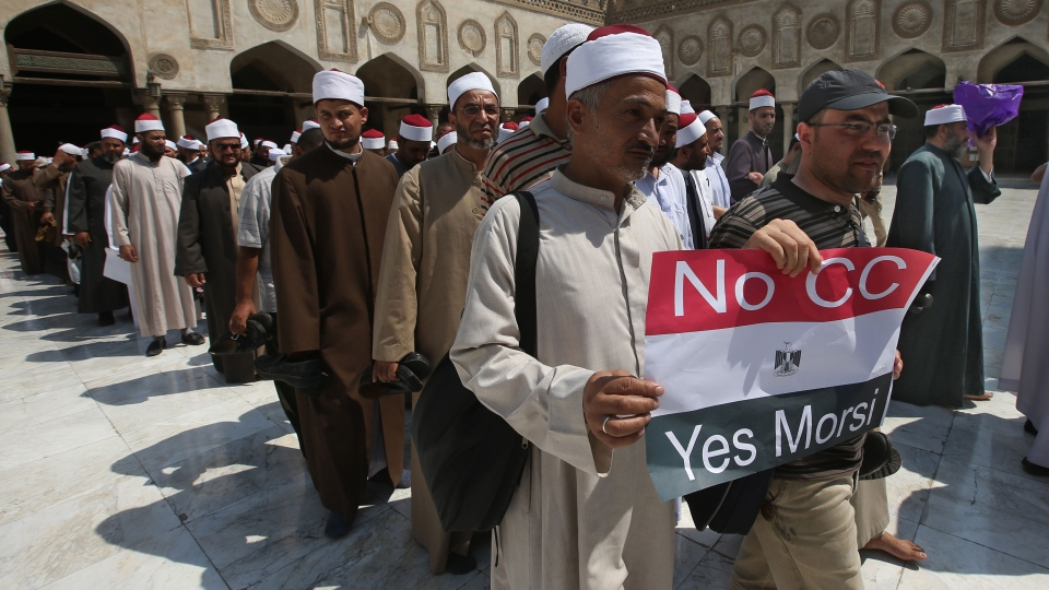 An Egyptian cleric and a supporter of ousted Egypt's President Mohammed Morsi hold up a placard against Egyptian Defense Minister General Abdul Fatah al-Sisi, as they leave with other clerics following a protest, at al-Azhar mosque in Cairo, Egypt, Sunday, July 14, 2013. (AP / Hussein Malla)