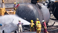 Firefighters clean up train crash site in Que.