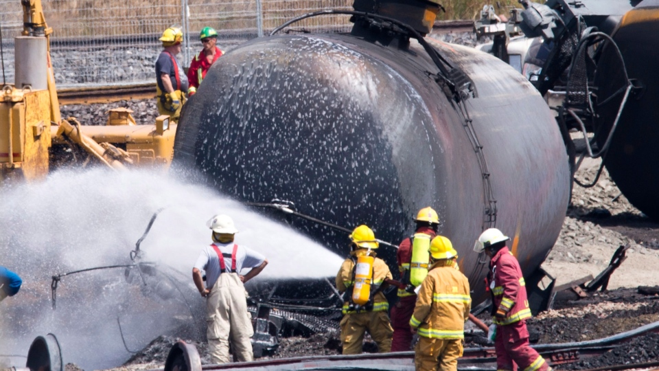 Firefighters spray foam on the train crash site in Lac-Megantic, Que., Sunday, July 14, 2013. (Jacques Boissinot / THE CANADIAN PRESS)
