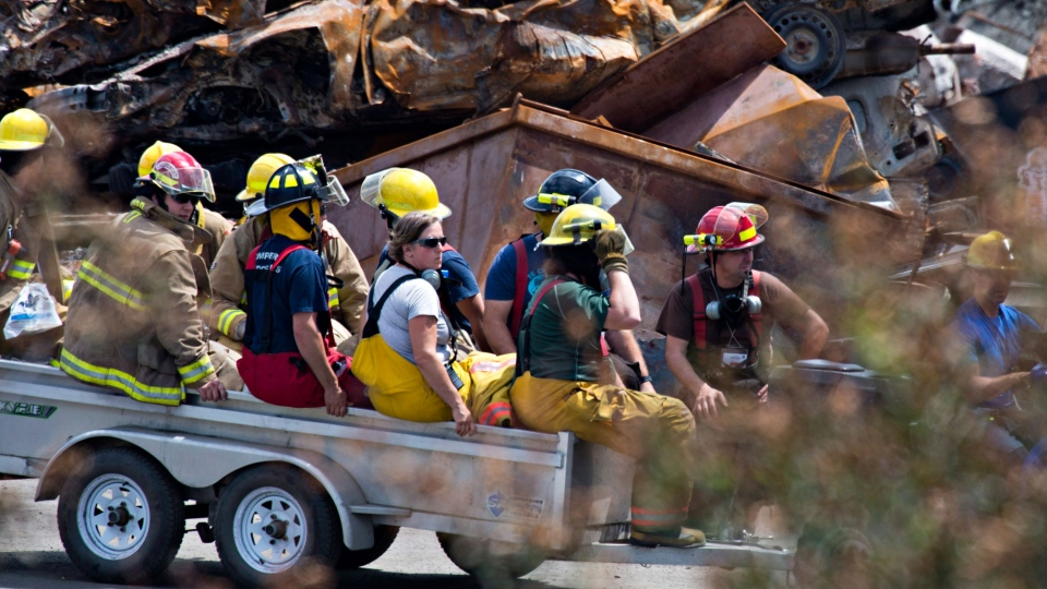 Firefighters are carried away from the train crash site in Lac-Megantic, Que., Sunday, July 14, 2013. (Jacques Boissinot / THE CANADIAN PRESS)