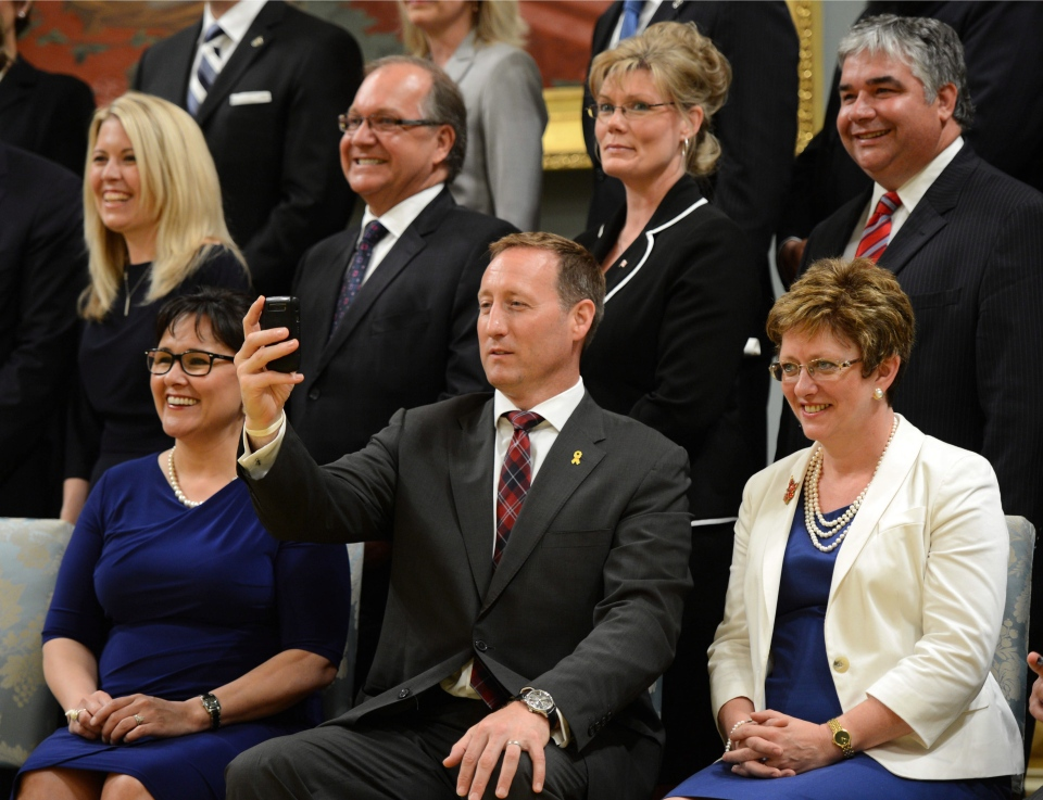 Minister of Justice and Attorney General of Canada Peter MacKay snaps a photo of the media as he sits beside Minister of Environment Leona Aglukkaq, left, and Minister of Public Works and Government Services Diane Finley during a cabinet group photo following a swearing in ceremony at Rideau Hall in Ottawa on Monday, July 15, 2013. (Sean Kilpatrick / THE CANADIAN PRESS)