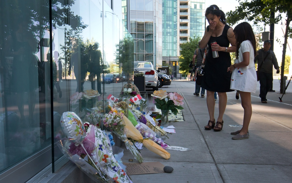 A woman reacts upon finding out Canadian actor Cory Monteith died as she pauses at a memorial for him outside the Fairmont Pacific Rim Hotel in Vancouver on Monday, July 15, 2013. (Darryl Dyck / THE CANADIAN PRESS)