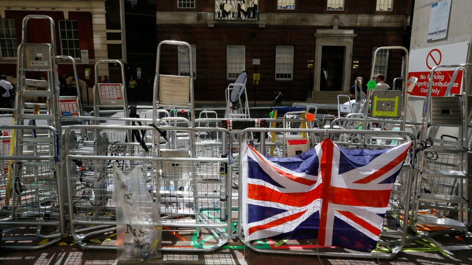 A Union Flag hangs on a barrier in front of media ladders outside the Lindo Wing at St Mary's Hospital in London, Monday, July 15, 2013. (AP / Kirsty Wigglesworth)
