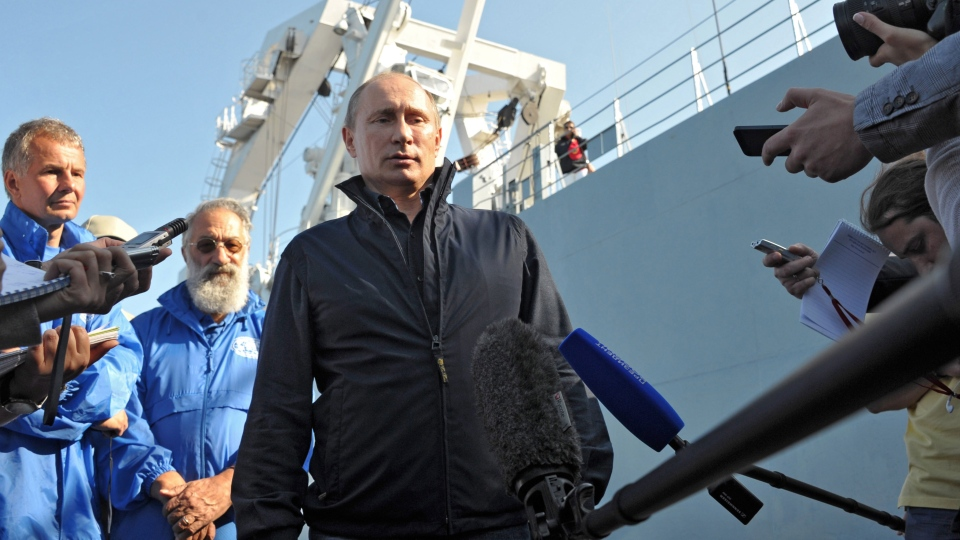 Russian President Vladimir Putin, centre, speaks to Russian media after he submerged on board Sea Explorer 5 bathyscaphe off the island of Gogland 180 kilometers (110 miles) west of St. Petersburg, Russia, on Monday, July 15, 2013. (RIA-Novosti, Alexei Nikolsky, Presidential Press Service)