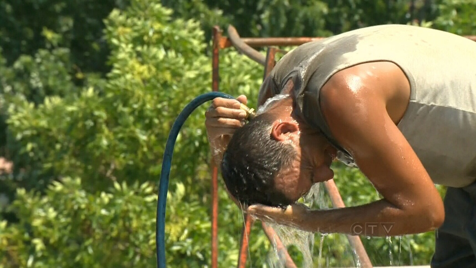 A construction worker drenches his head in water to cool off in Montreal, Monday, July 15, 2013.