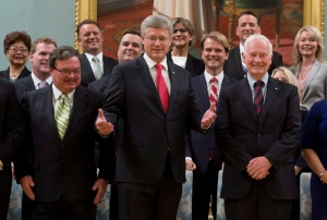 Prime Minister Stephen Harper gestures as she stands with members of his Cabinet following a swearing in ceremony at Rideau Hall in Ottawa on Monday, July 15, 2013. (Adrian Wyld / THE CANADIAN PRESS)