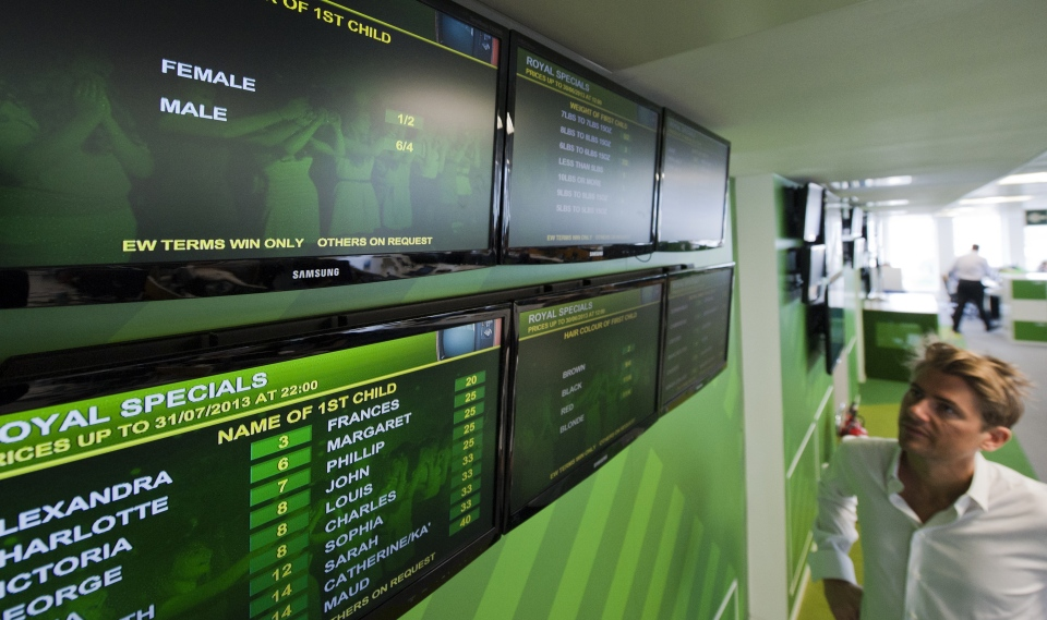 A person looks at screens offering odds on the gender, weight, name and hair colour of Britain's royal baby at a bookmakers in London on June 27, 2013 (AFP / WILL OLIVER)