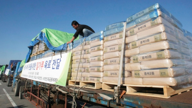 A South Korean truck driver works on sacks of flour for North Koreans before leaving for North Korean city of Kaesong at the Unification bridge near the Demilitarized Zone (DMZ) of Panmunjom at the Imjingak in Paju, South Korea, Thursday, Sept. 16, 2010. (AP / Ahn Young-joon)