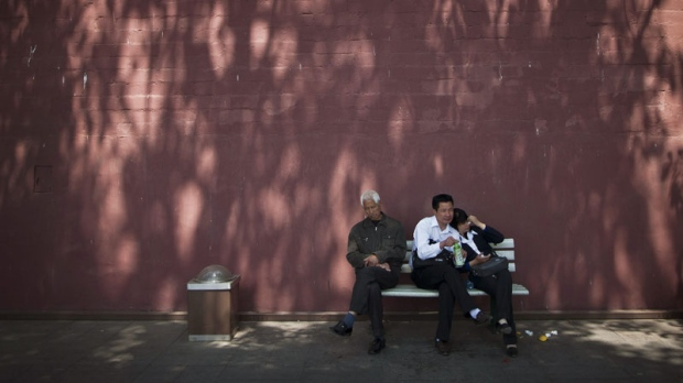 A Chinese couple and an elderly man take a rest on a bench near the Tiananmen Gate in Beijing, China Thursday, April 28, 2011. (AP Photo/Andy Wong)