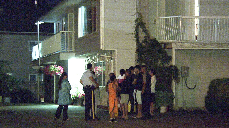 RCMP officers talk to residents after a five-year-old boy broke his leg in a fall from a second-storey window. (CTV)