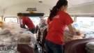 Volunteers load a school bus with hampers bound for Bowness and High River.
