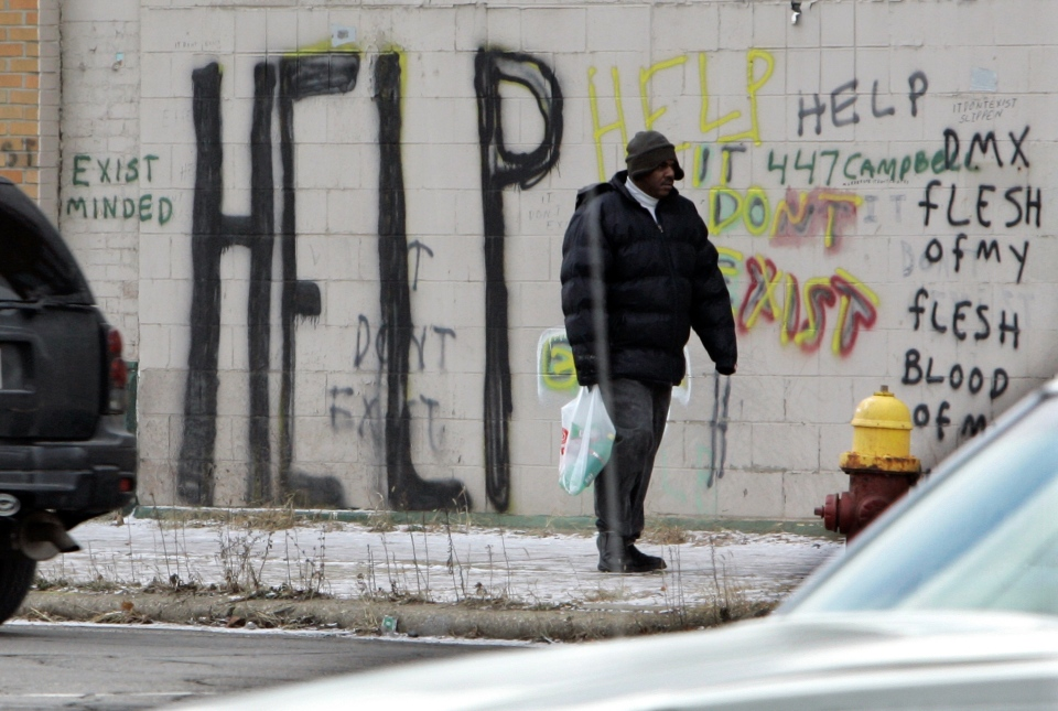 A pedestrian walks by graffiti in downtown Detroit, Dec. 12, 2008. (AP / Carlos Osorio)