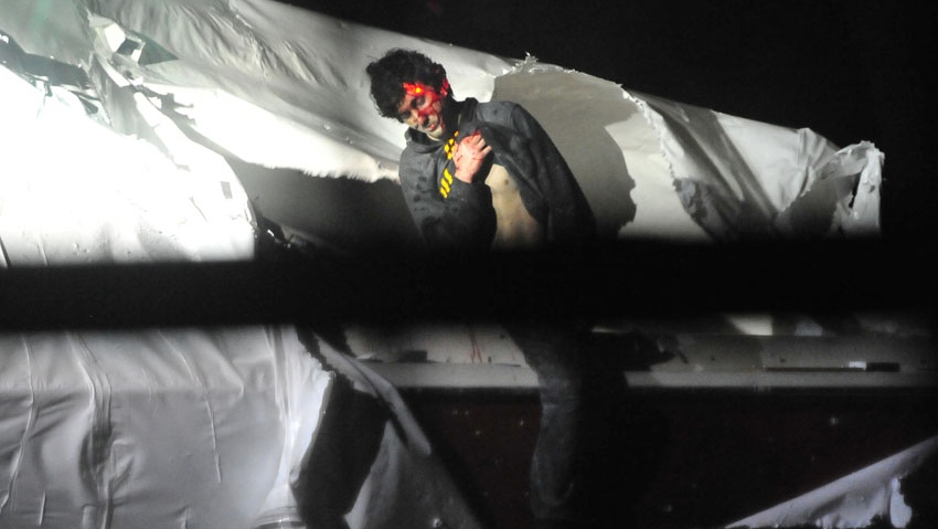 Boston bombing suspect Dzhokhar Tsarnaev raises his shirt during his arrest in this photo by Sean Murphy in Boston Magazine.
