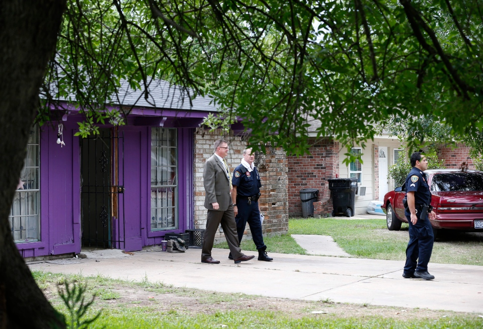 Authorities investigate a home, where police say four homeless men were found in deplorable conditions in Houston, Texas, Friday, July 19, 2013. (AP / Pat Sullivan)