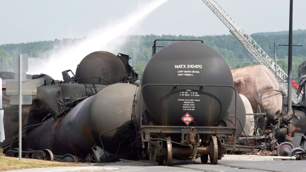 Fire fighters keep watering DOT-111 tanker cars railway cars the day after a train derailed causing explosions of railway cars carrying crude oil in Lac-Megantic, Que., Sunday, July 7, 2013. (Paul Chiasson / THE CANADIAN PRESS)