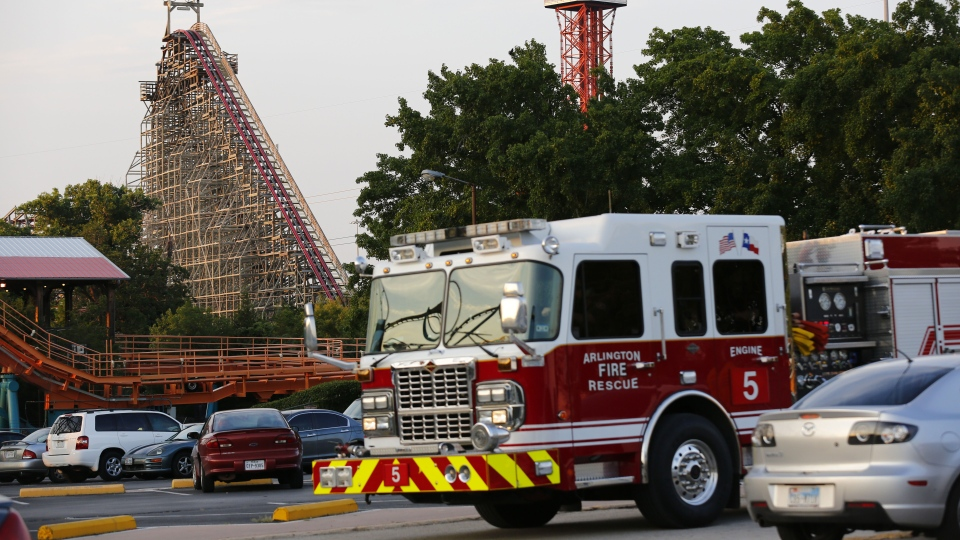 Emergency personnel are on the scene at Six Flags Over Texas in Arlington, Texas, after a woman died on the Texas Giant roller coaster, background left, on Friday, July 19, 2013. (The Dallas Morning News, Tom Fox)