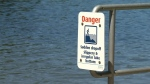 Signs at Thetis Lake, where a young person died Saturday, July 20, warn swimmers to be careful. (CTV)
