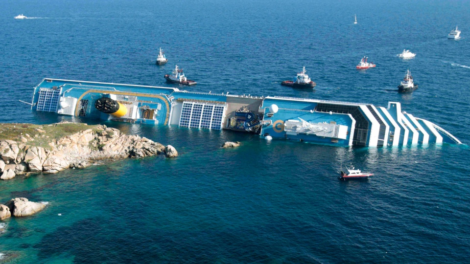 The luxury cruise ship Costa Concordia leans on its side after running aground in the tiny Tuscan island of Giglio, Italy, Jan. 14, 2012. (AP / Gregorio Borgia)