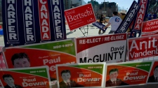 Pedestrians walk past the Government Conference Centre where Federal election signs are posted outside prior to the English language federal election debate in Ottawa Ont., on Tuesday, April 12, 2011. (Paul Chiasson / THE CANADIAN PRESS)