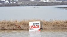 An election sign off Highway 11 soaks in high water in the Qu'Appelle Valley northwest of Regina on Sunday April 17, 2011. (Roy Antal / THE CANADIAN PRESS)