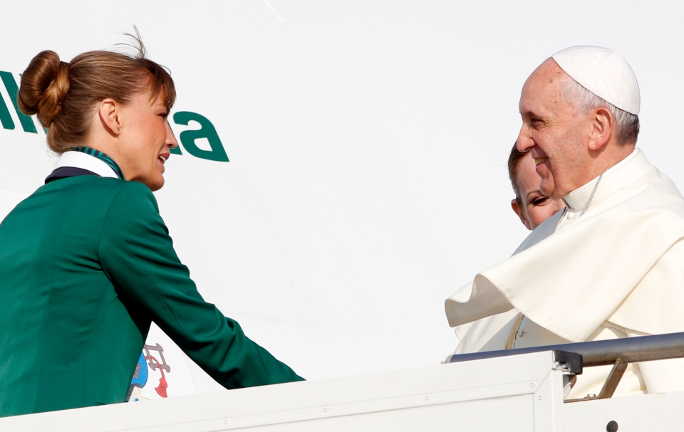 Pope Francis is welcomed by two hostesses as he boards a plane at Rome's Leonardo Da Vinci international airport, Monday, July 22, 2013. (AP / Riccardo De Luca)