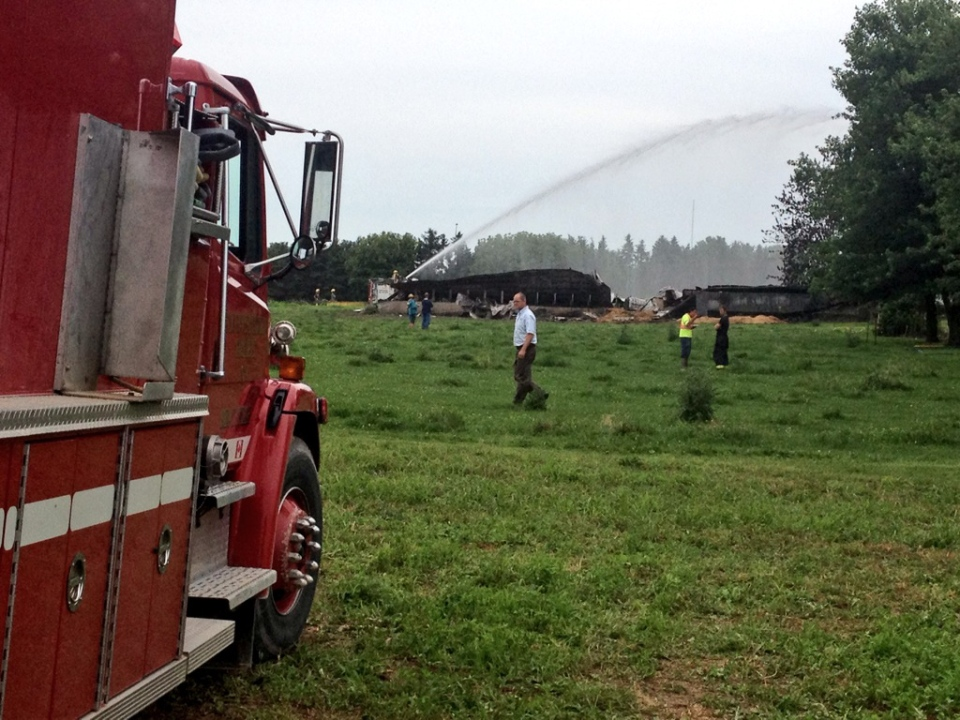 Firefighters deal with hotspots following a barn fire in South-West Oxford Township, Ont., on Monday, July 22, 2013. (Abigail Bimman / CTV Kitchener)