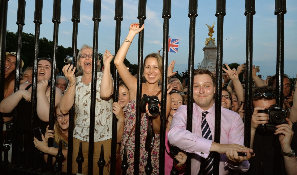 The large waiting crowds cheer as the Queen's Press Secretary Ailsa Anderson, with Badar Azim, a footman, place on an easel in the forecourt of Buckingham Palace a notification, to announce the birth of a baby boy, at 4:24 p.m. to the Duke and Duchess of Cambridge at St. Mary's Hospital in west London, Monday, July 22, 2013. (AP / John Stillwell)