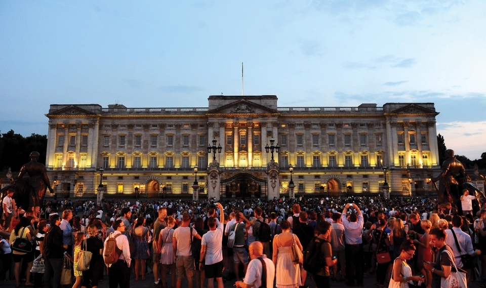 Members of the public celebrate outside Buckingham Palace after an easel was placed in the forecourt of the Palace with the notification to announce the birth of a baby boy, at 4:24 p.m. to the Duke and Duchess of Cambridge at St Mary's Hospital in west London, Monday, July 22, 2013.(AP / Clive Gee, PA)