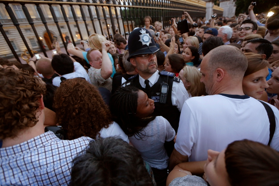 A police officer, centre, tries to control a crowd of people trying to get to the railing to take pictures of a notice proclaiming the birth of a baby boy to Prince William and Kate, Duchess of Cambridge on display for public view at Buckingham Palace in London, Monday, July 22, 2013. (AP / Sang Tan)