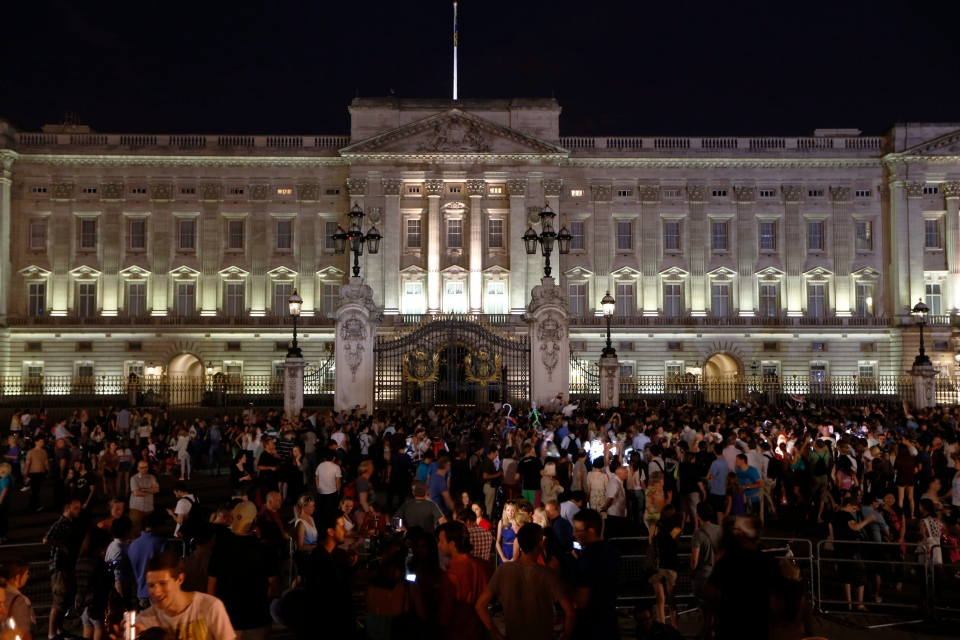 People gather outside a floodlit Buckingham Palace in London to mark the birth of a baby boy to Prince William and Kate, Duchess of Cambridge, Monday, July 22, 2013. (AP / Sang Tan)