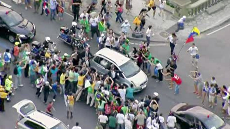 In this image from video, a crowd mobs the silver Fiat carrying Pope Francis through Rio de Janeiro on Monday, July 22, 2013. (AP)