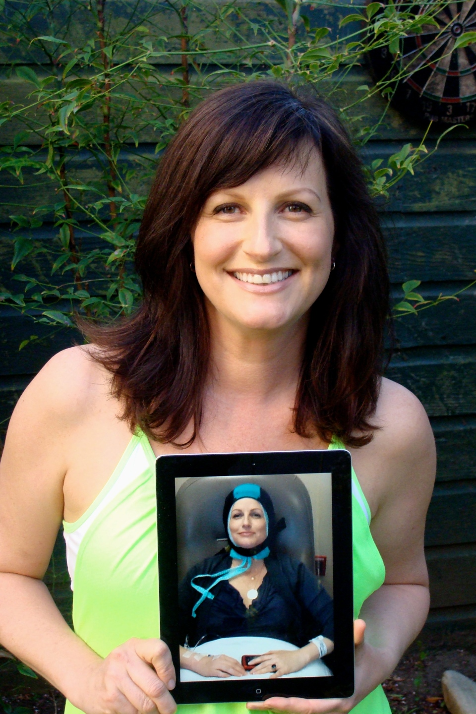 Breast cancer survivor Miriam Lipton, of San Francisco, holds a picture of herself, while undergoing chemotherapy two years ago wearing the DigniCap, an experimental scalp-cooling system that she credits with preserving most of her hair, June 20, 2013. (AP)