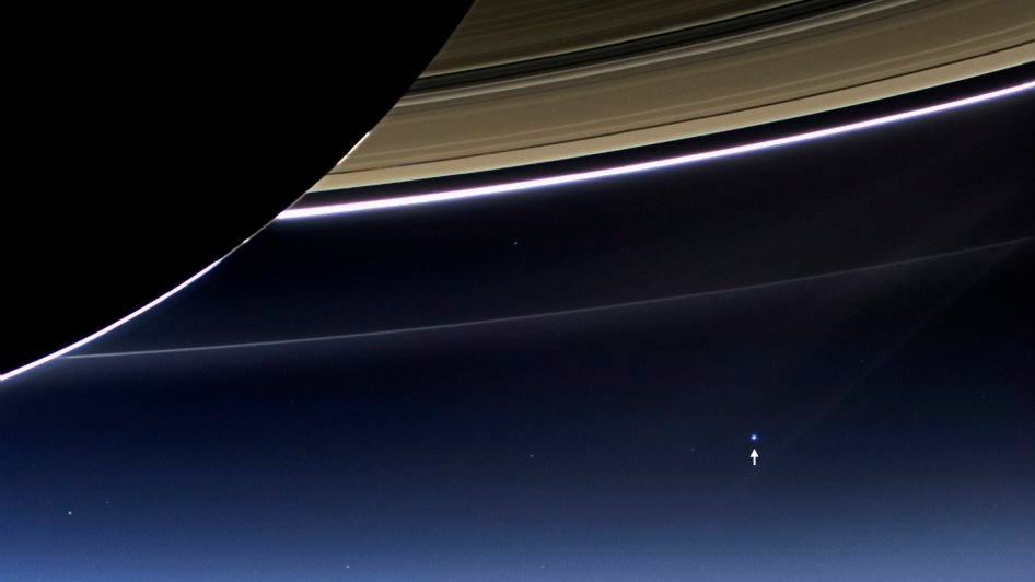 This July 19, 2013 image from the Cassini spacecraft provided NASA shows the planet Earth, annotated by NASA with a white arrow, lower right, below Saturn's rings. (AP Photo/NASA/JPL-Caltech/Space Science Institute)