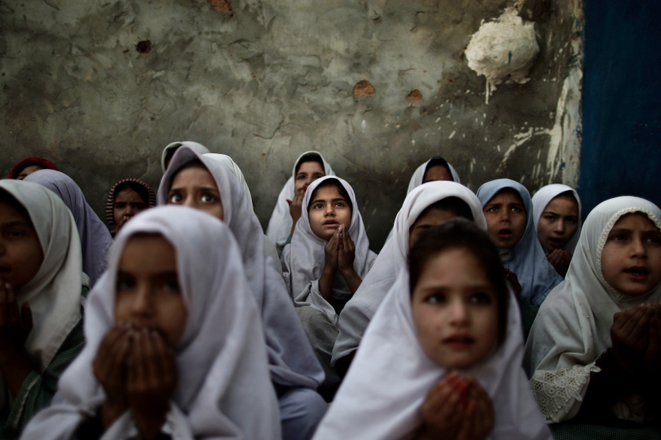 Pakistani schoolgirls, who were displaced with their families from Pakistan's tribal areas due to fighting between militants and the army, chant prayers during a class to pay tribute for five female teachers and two aid workers who were killed by gunmen, at a school, on the outskirts of Islamabad, Pakistan in this Thursday, Jan. 3, 2013 photo. (AP / Muhammed Muheisen)