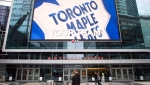 Pedestrians walk past the Air Canada Centre as a screen projects an image of the Toronto Maple Leafs logo in Toronto on Wednesday, Dec. 1, 2010. (The Canadian Press/Darren Calabrese)