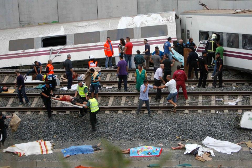 Emergency personnel respond to the scene of a train derailment in Santiago de Compostela, Spain, Wednesday, July 24, 2013. (AP / El correo Gallego / Antonio Hernandez)