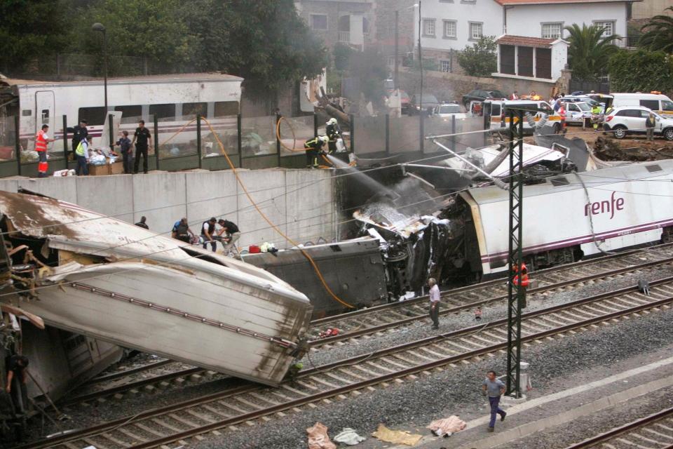 Emergency personnel respond to the scene of a train derailment in Santiago de Compostela, Spain, Wednesday, July 24, 2013. (El correo Gallego / Antonio Hernandez)