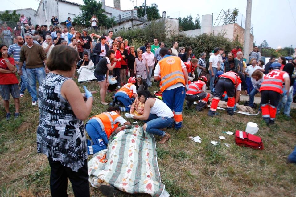 Emergency personnel respond to the scene of a train derailment in Santiago de Compostela, Spain, on Wednesday, July 24, 2013. (El correo Gallego / Antonio Hernandez)