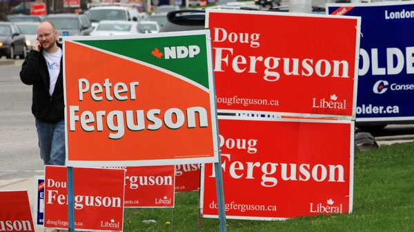 Pedestrians and motorists pass election signs for Ed Holder of the Conservatives and two Ferguson candidates, Doug for the Liberals and Peter for the NDP in the London West riding, in London, Ontario, Monday, May 2, 2011. (Dave Chidley / THE CANADIAN PRESS)
