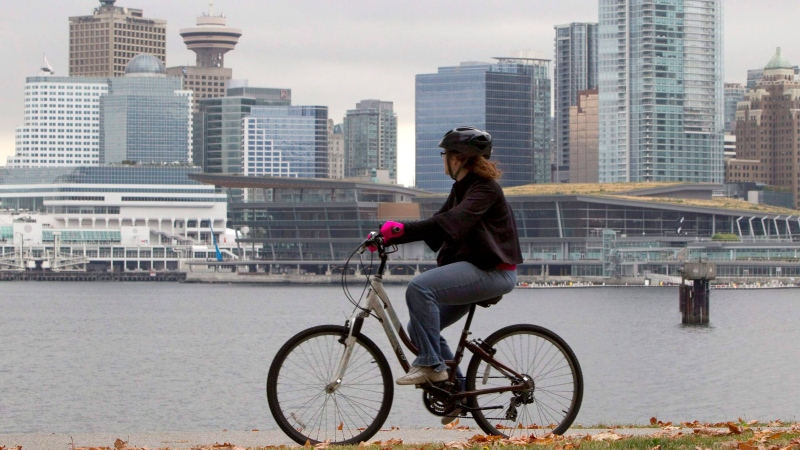 A cyclist rides her bike along the seawall in Stanley Park in downtown Vancouver, Sept. 16, 2011. (Jonathan Hayward / THE CANADIAN PRESS)