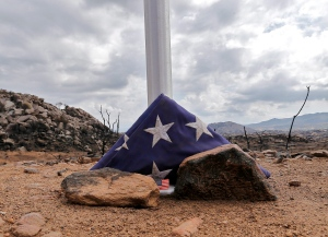 A flag sits at the base of a flag pole at the site where 19 firefighters died battling an Arizona wildfire on June 30th is shown Tuesday, July 23, 2013 in Yarnell, Ariz. (AP / Matt York)