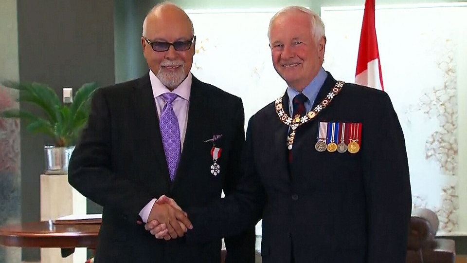 Rene Angelil shakes Gov.-Gen. David Johnston's hand after being presented with an insignia officially naming him as a Member of the Order of Canada, in Quebec City, Friday, July 26, 2013.