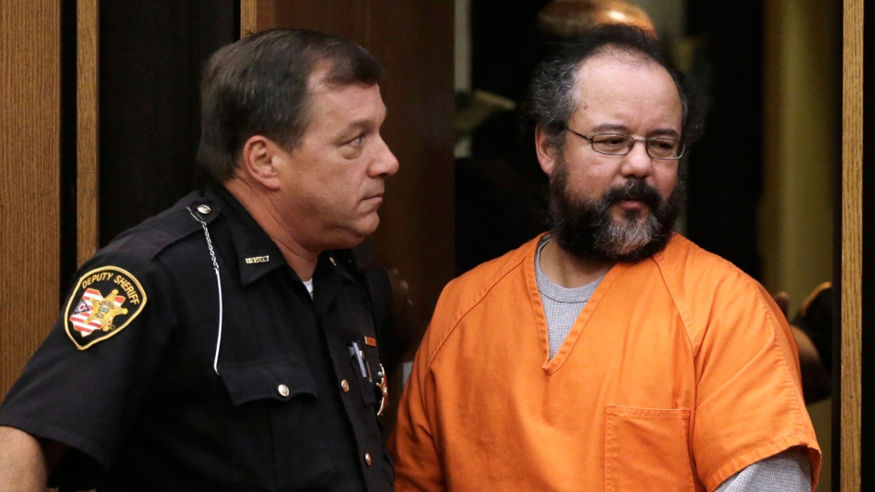 Ariel Castro, right, walks into the courtroom watched closely by a deputy sheriff in Cleveland, Friday, July 26, 2013. (AP / Tony Dejak)