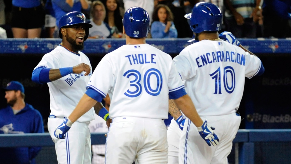Toronto Blue Jays' Jose Reyes (right) Josh Thole and Edwin Encarnacion celebrate Encarnacion's grand slam against the Houston Astros during seventh inning AL baseball game action Friday July 26, 2013 in Toronto. (Jon Blacker / THE CANADIAN PRESS)