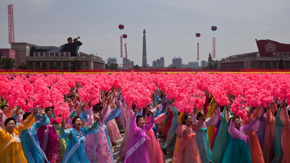 North Korean women wave to their leader Kim Jong Un during a mass military parade on Kim Il Sung Square in Pyongyang to mark the 60th anniversary of the Korean War armistice, Saturday, July 27, 2013. (AP / David Guttenfelder)