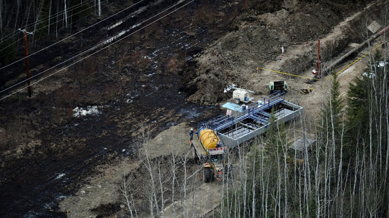 Workers collect oil in bins during the cleanup of a pipeline break northeast of Peace River, Alta., on Wednesday May 4, 2011. (THE CANADIAN PRESS\Ian Jackson)