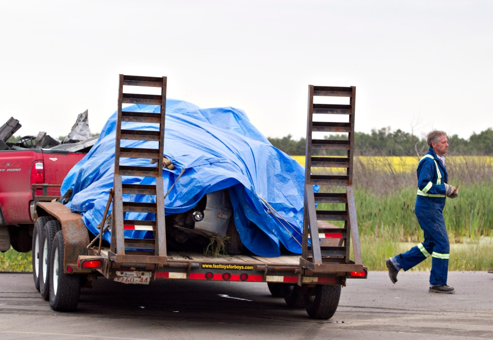 A trapped up vehicle sits on a trailer after it was involved in a collision with a semi near Lloydminster, Sask., on Saturday, July 27, 2013. (Jason Franson / THE CANADIAN PRESS)