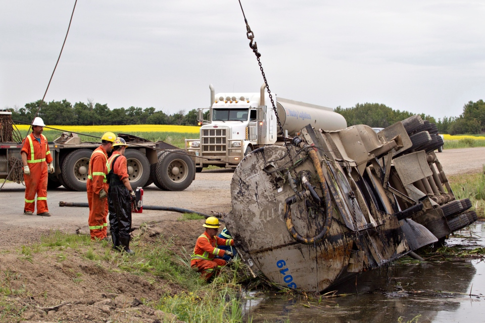 Crews work to pull a semi out of a pond that was involved in a collision with another vehicle near Lloydminster, Sask., on Saturday, July 27 2013. (Jason Franson / THE CANADIAN PRESS)